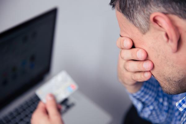 upset man viewing his credit card